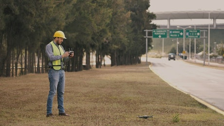 Man in hard hat flying drone on side of the road