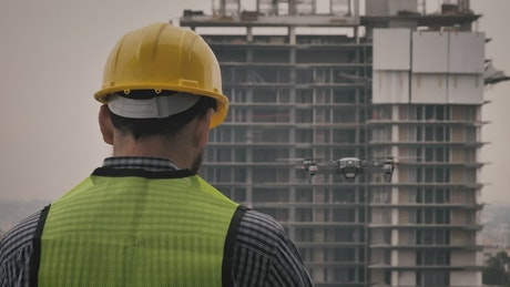 Man in hard hat watching drone fly