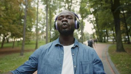 Man in headphones dances hiphop in park