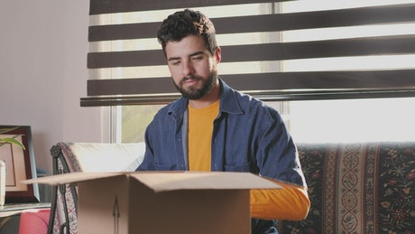 Man in his living room finishes packing a box to ship