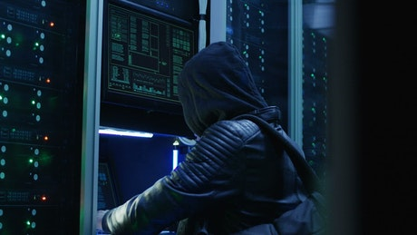 Man in hoodie hacking a data center