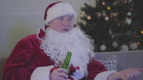 Man in Santa costume drinks beer on sofa