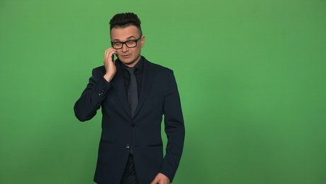 Man in suit and glasses answering a phone call