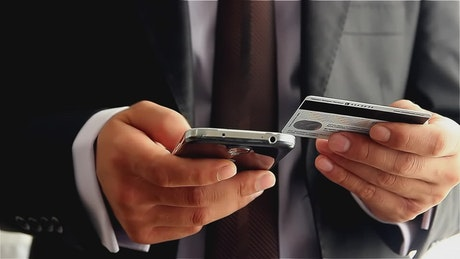 Man in suit copying data from a card in his cell