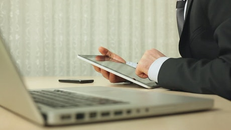 Man in suit using a tablet next to his computer