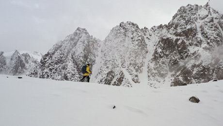 Man in yellow coat climbing ridge in Himalayas