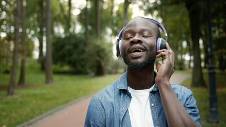 Man inspired by music while on walk in park