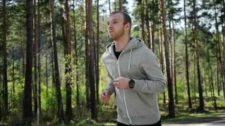 Man jogging in forest checks GPS watch