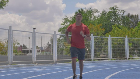 Man jogging on a running track on a sunny day