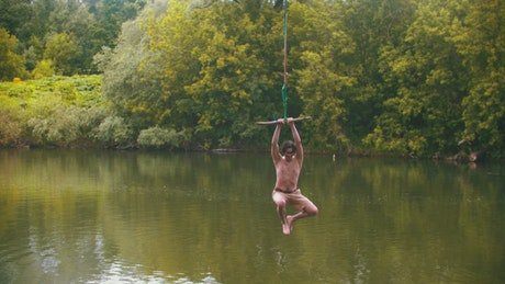 Man jumps into a lake by swinging with a rope