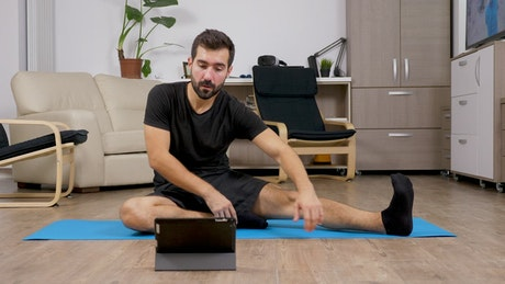 Man learning exercises from online video at home