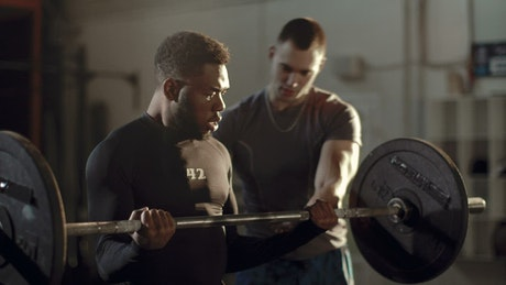 Man lifting weights supported by his trainer