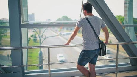 Man looking from a pedestrian bridge