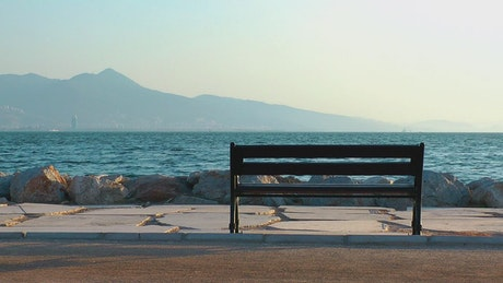 Man looking out to sea at the pier from a bench