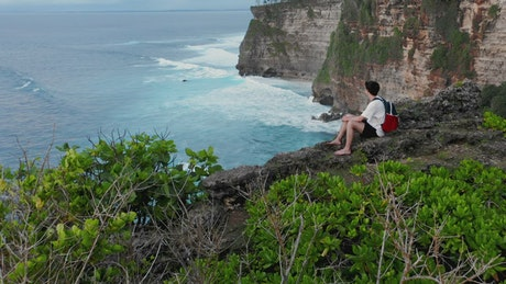 Man looks over cliff edge to sea on Bali Indonesia
