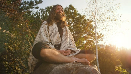 Man meditating deeply at sunset in nature