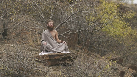 Man meditating deeply in an autumnal forest