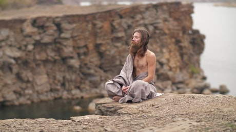 Man meditating on the hill by the sea