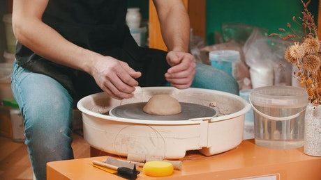 Man molding clay on the spinning wheel