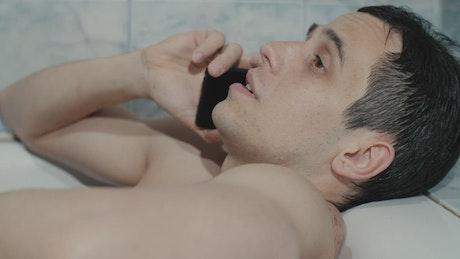 Man on a call while taking a bath