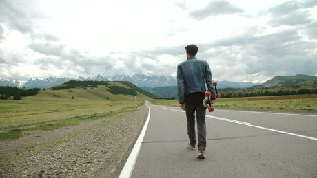 Man on a longboard on the road