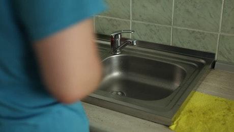 Man on diet washing vegetables in sink