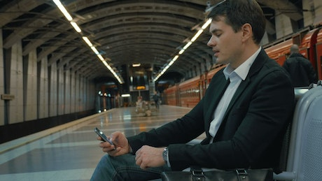 Man on his phone waiting for a train