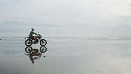 Man on motorcycle on the seashore