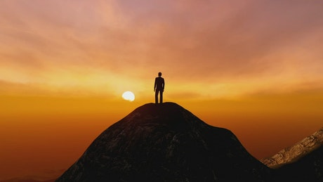 Man on the top of a mountain watching the sunset