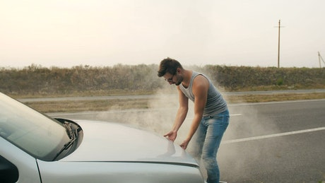 Man opening the hood of his broken down car