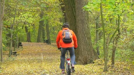 Man pedaling through the park in autumn