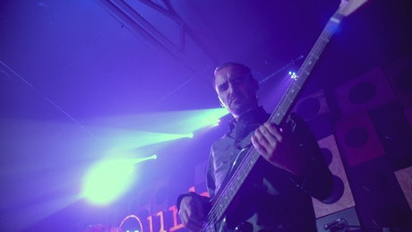 Man playing a bass guitar on a stage