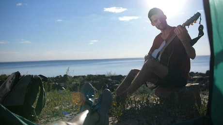 Man playing a guitar while camping