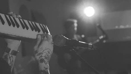 Man playing a keyboard in front of a microphone