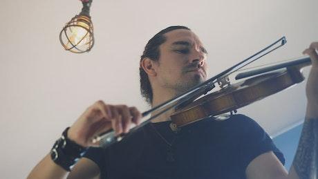 Man playing a violin indoors