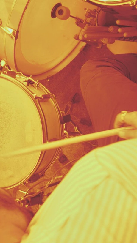 Man playing drums with sepia filter