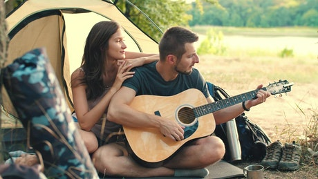 Man playing guitar to his girlfriend in camp