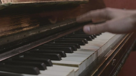 Man playing on an old piano
