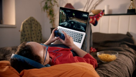 Man playing video games lying in his room