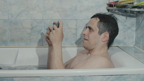 Man playing with his cell phone while taking a bath