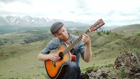 Man plays acoustic guitar on ridge above mountain landscape