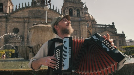 Man plays an accordion in front of a fountain and church