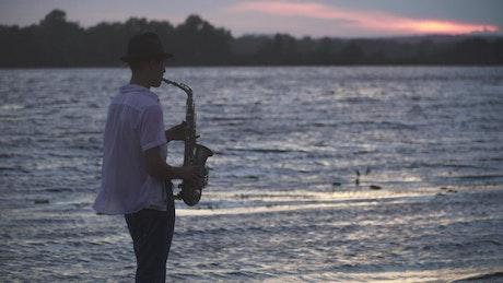 Man plays saxophone to ducks by lake at sunset
