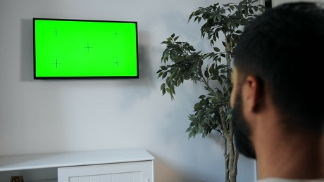 Man points remote at green screen TV on wall