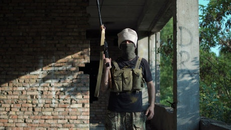 Man posing with a gun on an abandoned site