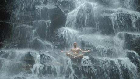 Man practicing mind body meditation in waterfall