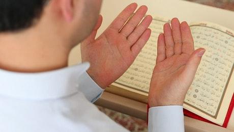 Man praying before the Quran