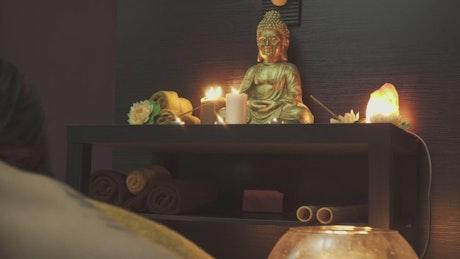 Man praying to candle-lit Buddha