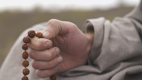 Man praying with a rosary, close up of hands