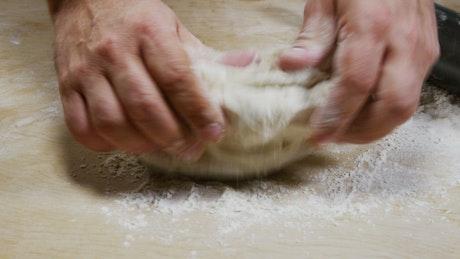 Man preparing pizza dough in the kitchen